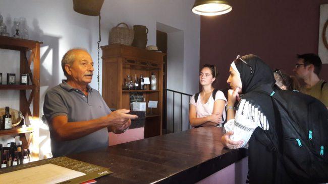 El gerente de la almazara, Laureano Sígler, muestra a los visitantes los diferentes productos en la tienda de la almazara.